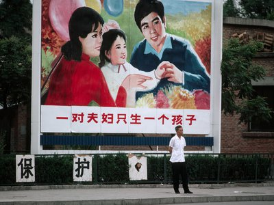 A man walks by a family planning billboard portraying parents and one child in Beijing in 1983. China just announced it will reverse its controversial one-child policy.