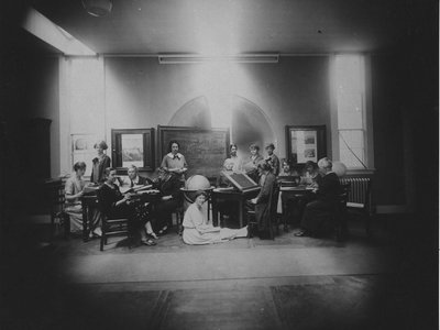 Margaret Harwood sits on the floor for this posed tableau taken on May 19, 1925. Harvia Wilson is at far left, sharing a table with Annie Cannon (too busy to look up) and Antonia Maury (left foreground). The woman at the drafting table is Cecilia Payne.