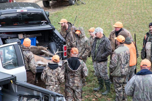 Hunters gather around a Whitetail buck. thumbnail
