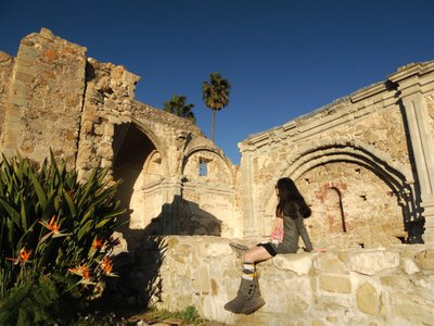 A woman sits amid the ruins of the Great Stone Church, which collapsed in an 1812 earthquake, at Mission San Juan Capistrano.