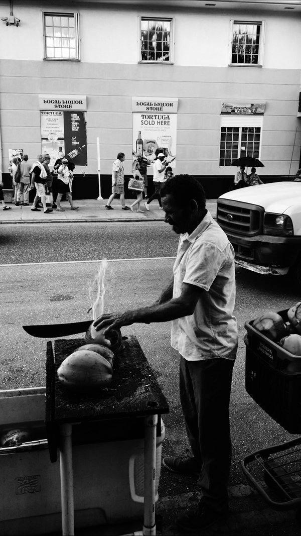 A native islander cracking a coconut with a machete. thumbnail