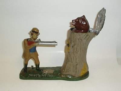 In this intricate mechanical bank, the user balances a coin on the miniature man's gun, which then shoots the coin into a slot in the tree.
