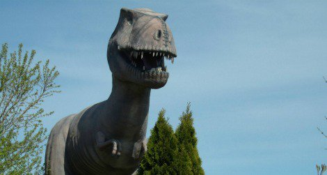 A Tyrannosaurus stands over the remains of an abandoned mini-golf course.