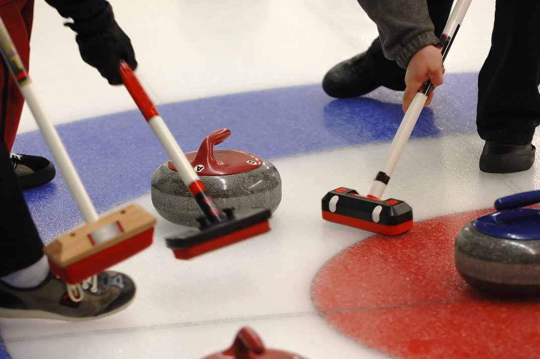 Image of curling stones and sweepers