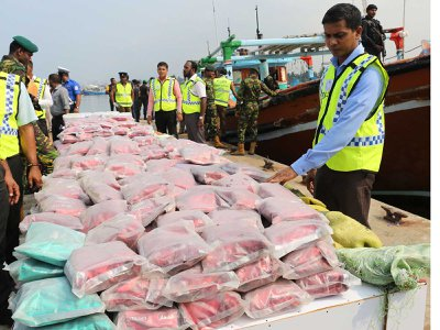 Sri Lankan police stand next to over $33 million worth of heroin and crystal methamphetamine seized from two foreign trawlers.