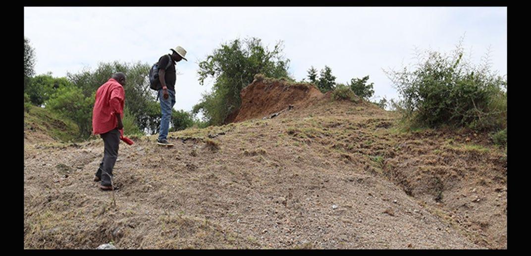 Two people climb a barren hill in Kenya