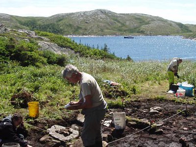 Bill Fitzhugh maps the blacksmith's shop's floor, 2008.  The Smithsonian research vessel PItsuilak rides at anchor in the bay.  Fitzhugh and his team live aboard the boat, which takes its name from the Inuit word for a seabird, during their excavations.
