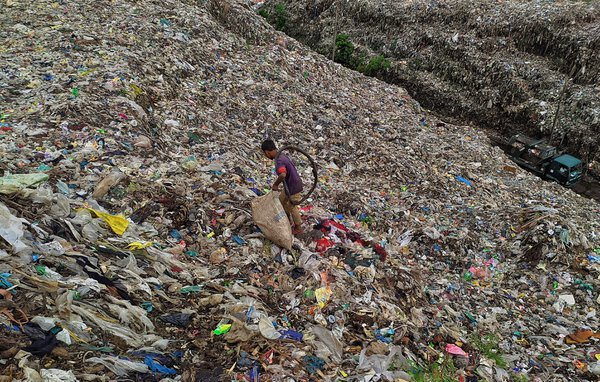 A boy picks up paper, plastic, lying in a pile of rubbish. thumbnail