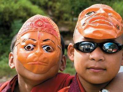 """Tradition and change coalesce (young monks at a religious festival sport trendy shades, masks and a swastika—for Buddhists, a symbol of good fortune) in the remote, majestic country its citizens call Druk Yul or """"Land of the Thunder Dragon."""""""