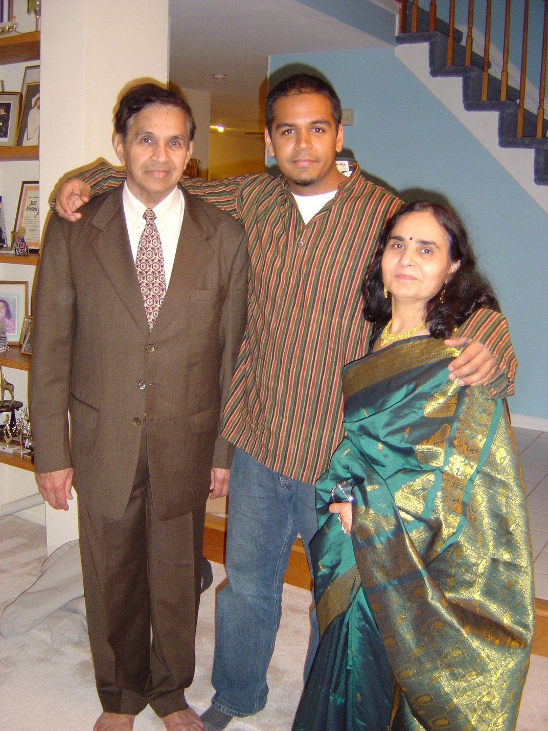 Photo of the author posing with his arms around his mother and father. They are all dressed up for a special occasion, the men in Western dress suits and the mom is traditional South Asian dress.
