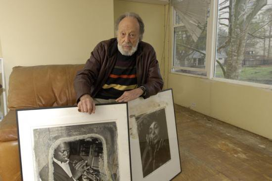 Man poses with two large black and white photo prints