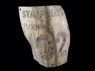 """This damaged floor marker, labeled """"Stairwell C, Floor 102,"""" was recovered from the debris of the World Trade Center and is now housed in the National Museum of American History's National September 11 Collection."""