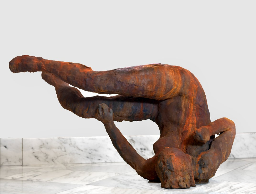 A bronze sculpture of a person who has fallen and landed on her head, her body in the air