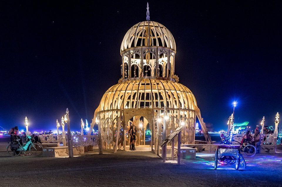 A photograph of a wooden temple being built at night in the dessert.