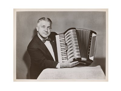 Photograph of John Vassos holding the Marchesa model accordion he designed for M. Hohner, 195-? / unidentified photographer. John Vassos papers, 1915-1989. Archives of American Art, Smithsonian Institution.