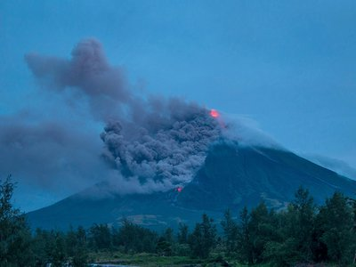 Lava cascades down the slopes of the erupting Mayon volcano in January 2018. Seen from Busay Village in Albay province, 210 miles southeast of Manila, Philippines.