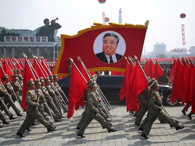 North Korean soldiers carry flags and a photo of late leader Kim Il-sung during a military parade on Saturday, April 15, 2017, in Pyongyang, North Korea.