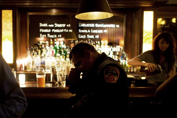 A NYC fireman rests his head at a Zablowski's bar in Brooklyn on the evening of September 11, 2009. thumbnail