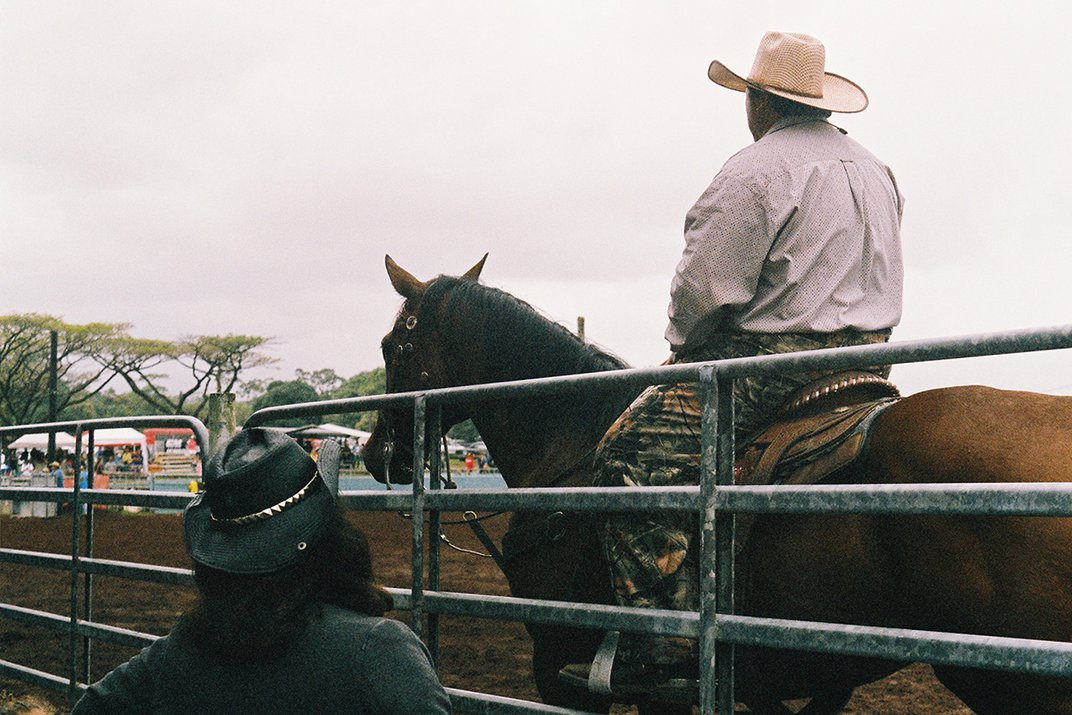 A person in a cowboy hat sits atop a horse, standing next to another person in cowboy hat on the other side of a gate.