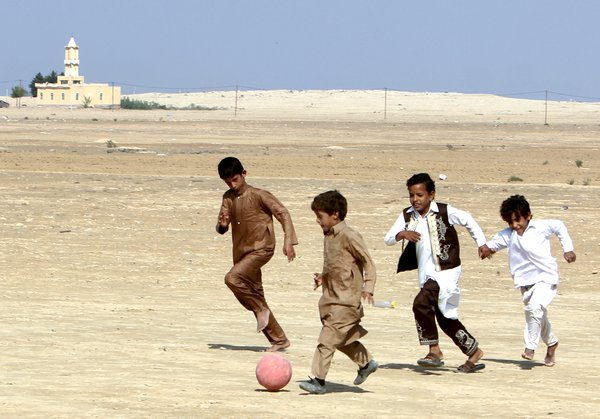 Children playing football in the desert thumbnail