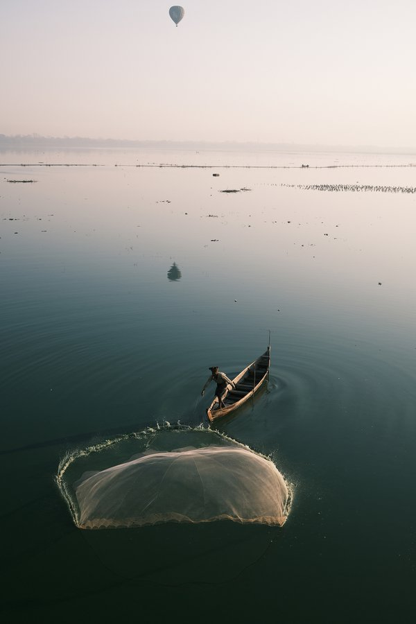 The fisherman from Mandalay is throwing the net in the lake.