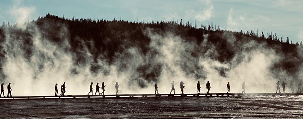 People walking on path with steam from geyers thumbnail