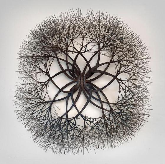 Bronze wire sculpture with the center roughly in a star shape with edges expanding outward like tree branches.
