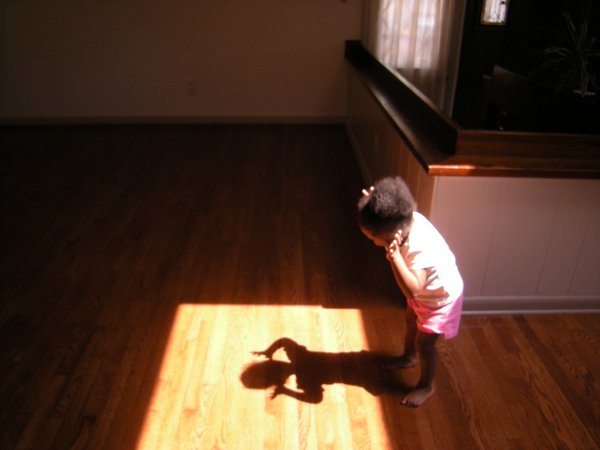 Peek-A-Boo.  Little girl discovers her shadow. thumbnail