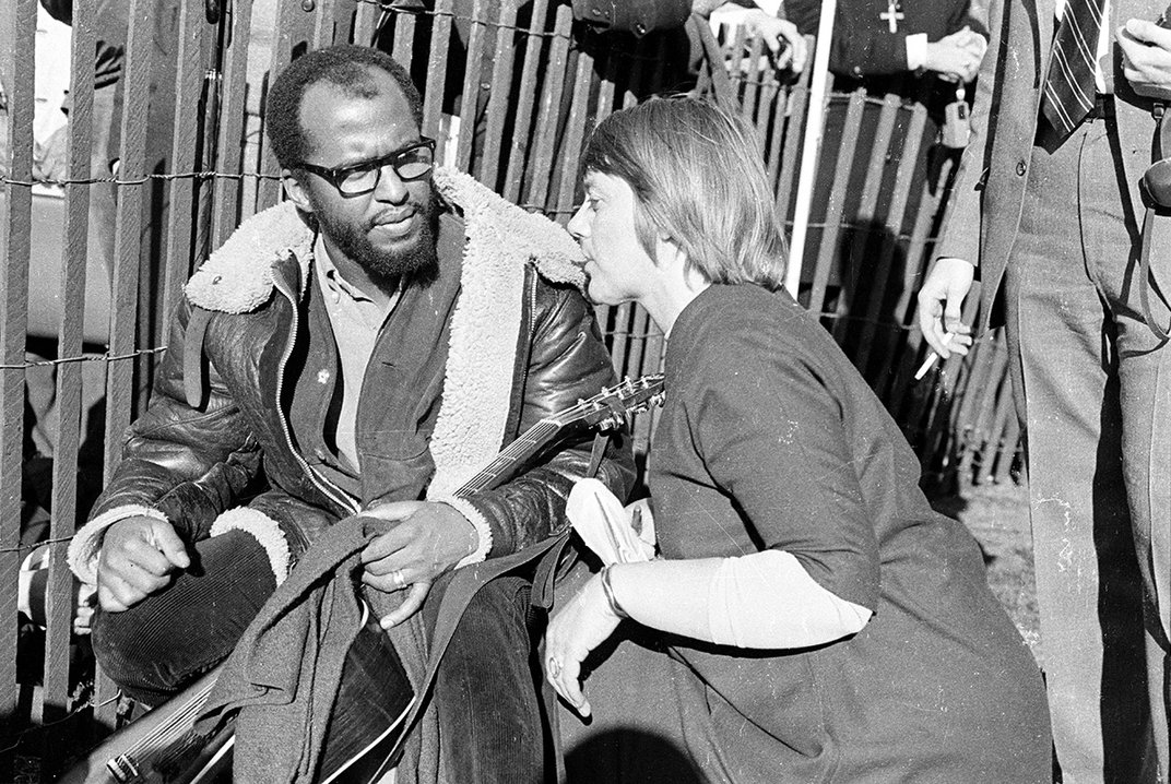 Woman talks with man in a leather jacket holding an acoustic guitar, both sitting on the ground alongside a picket fence.