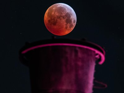 A picture taken on January 21, 2019 in Duisburg, Germany, shows a view of the Super Blood Moon above an industrial plant during a lunar eclipse.