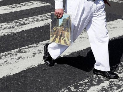 A fan carries a copy of 'Abbey Road' as he traverses the infamous crosswalk that appears on the album's cover.