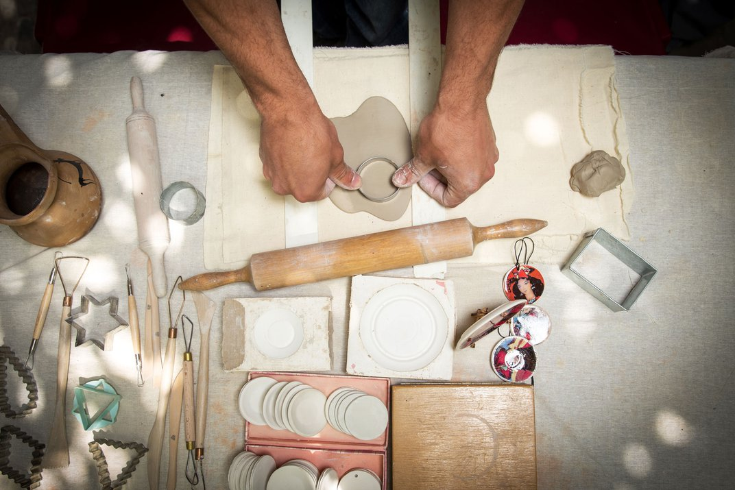 Spread out on a table are a variety of pottery tools and shape cutters. In the middle of the table is a rolled out piece of clay about to be cut with a circular shape.