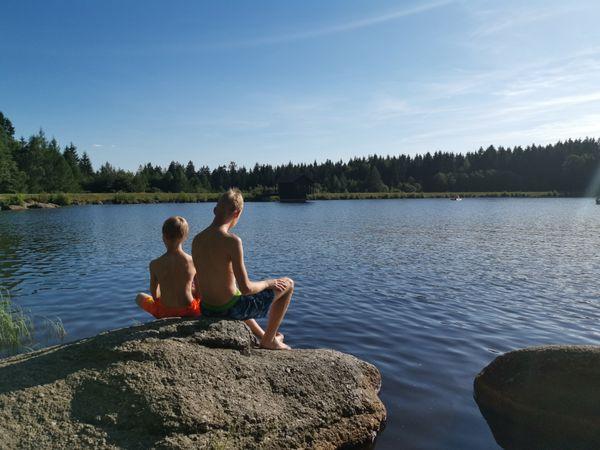 Two boys sitting on a rock at a lake thumbnail