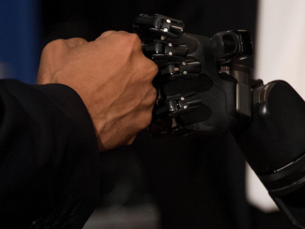 President Barack Obama fist bumps a robotic arm