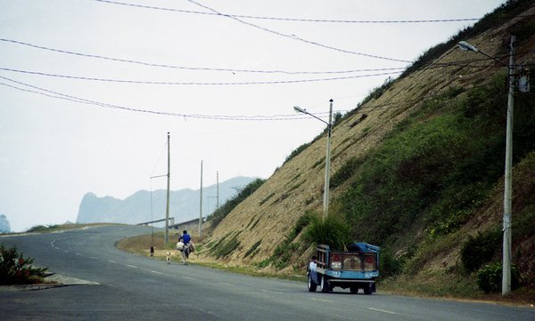 An old truck chases a man on a burro on a winding road on the coast of Ecuador. thumbnail