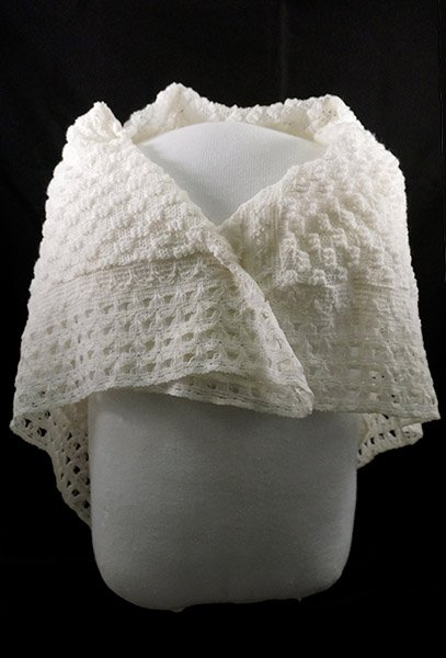 White shawl wrapped around mannequin's shoulders