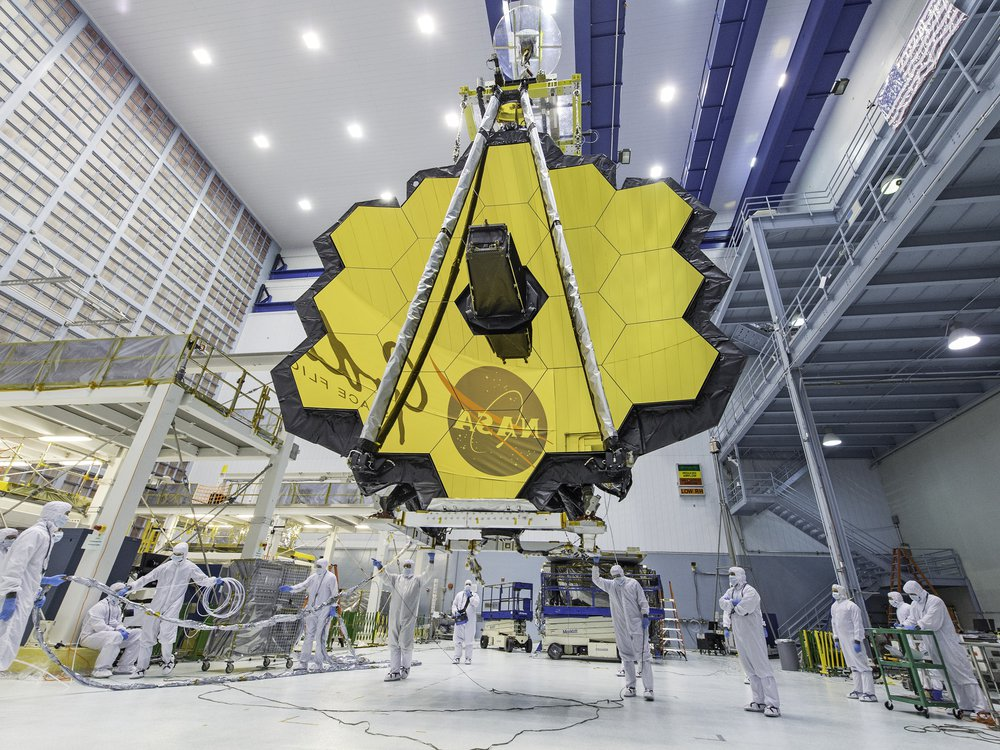 An image of the James Web Telescope in a NASA laboratory. Technicans are seen standing under it while the honey come shaped telecope mirror hangs above. The NASA logo is seen reflected in the mirrors.