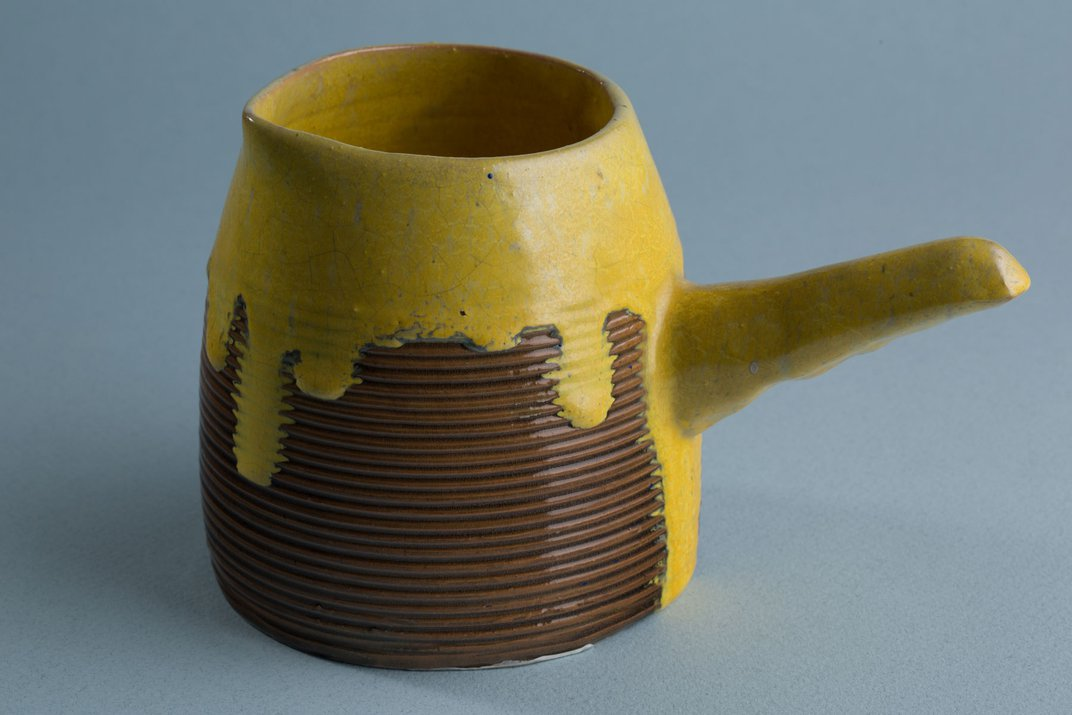 A ceramic pot glazed at the top with a bright yellow glaze, dripping down its sides. The bottom of the pot is glazed in a warm brown and has a ribbed texture.