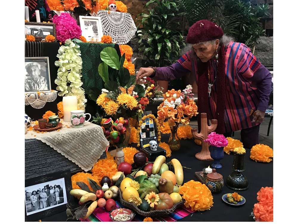 Doña Ofelia Esparza decorates the ofrenda