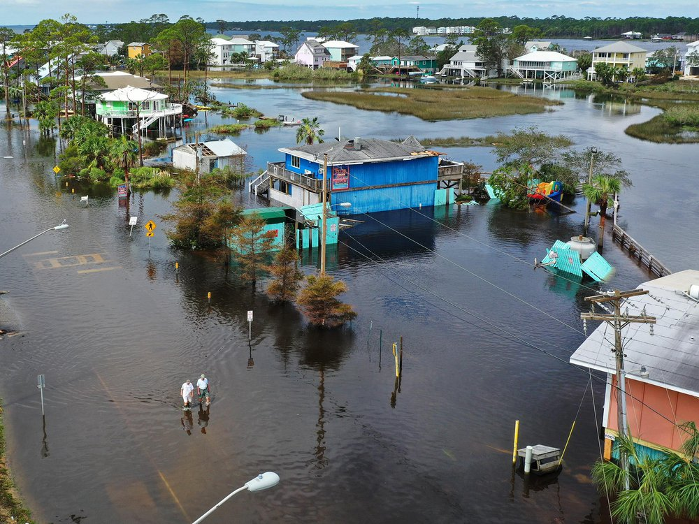 A flooded neighborhood from a bird's eye perspective, with two small figures walking in water that comes up to their calves. The street is entirely submerged, as are the foundations of the colorful houses