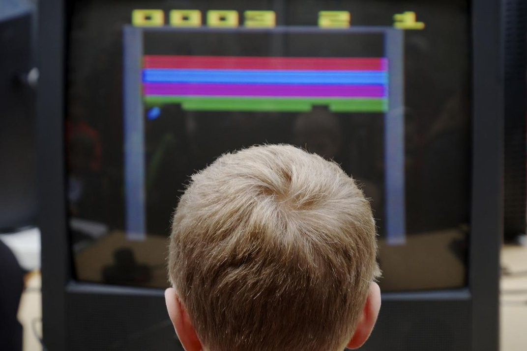 Back of boy's head that is looking at a TV screen with video game on it.