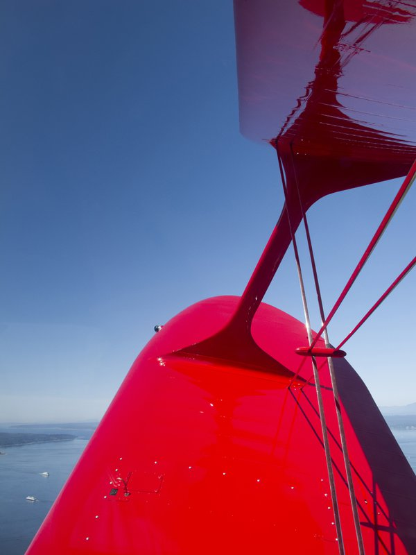 Red biplane wings over Puget Sound thumbnail