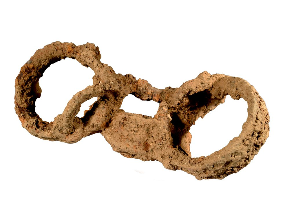 An image of a very rusted pair of shackles, two circles connected by a padlock that would have encircled someone's ankles