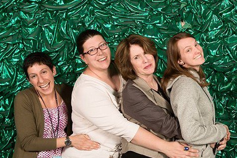 Four Caucasian women pose for a photo in front of a green backdrop