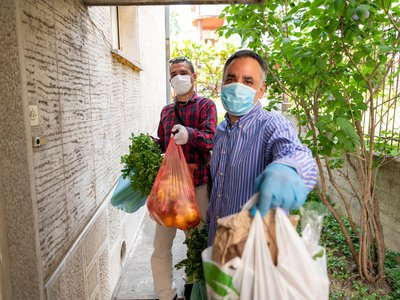 """""""Engaged philanthropy is vital to democracy,"""" writes Smithsonian scholar Amanda B. Moniz, who studies the history of giving in America. Above: charity workers bring groceries to those isolating with symptoms of Covid-19."""