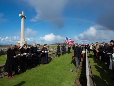 As we gathered at the graveyard, facing the sea and a memorial to the deceased, rain clouds parted, and the crowd was moved by the appearance of a rainbow.