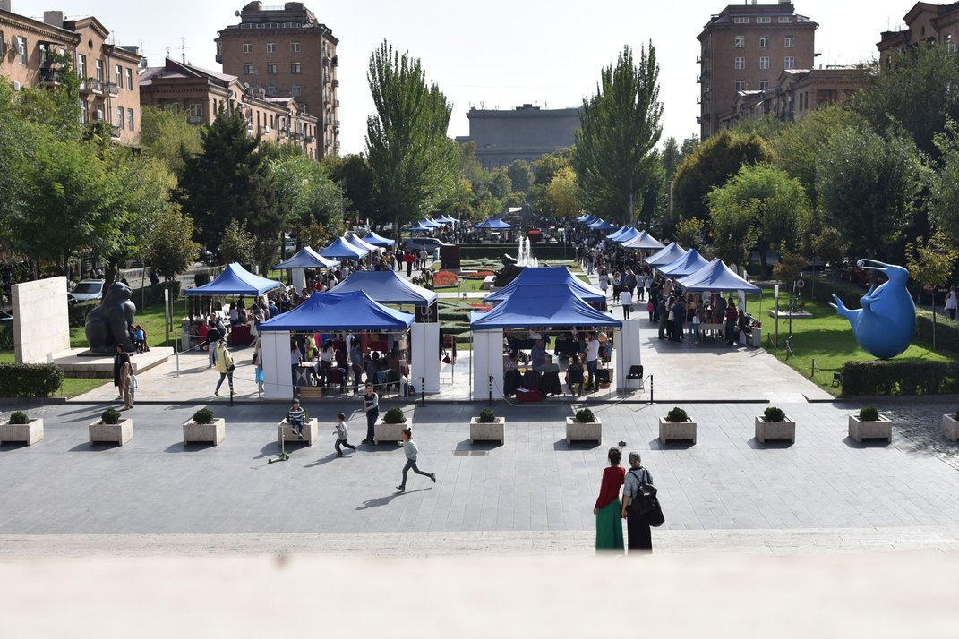 A large rectangular sculpture park is filled with blue tents for vendors.  In front of the tents is a patio where children play.