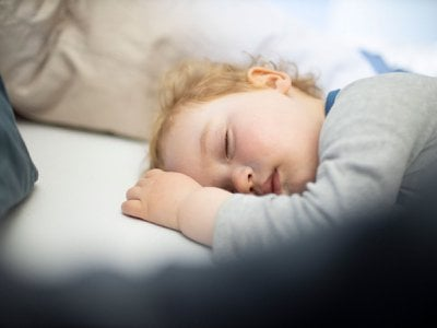 A child sleeps in his parents bed.