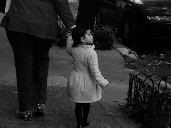 An inquisitive little girl in the Upper East Side. Soft in step, driven by the hand of a mother with rough, worn feet. thumbnail