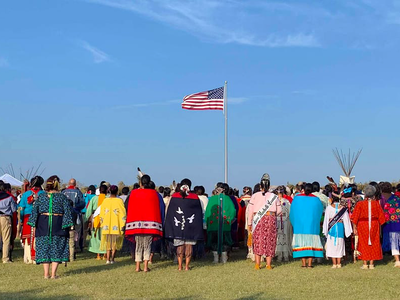 """Members of the Kiowa Gourd Clan Ceremony stand as the flag of Spencer """"Corky"""" Sahmaunt is raised. Carnegie, Oklahoma; July 4, 2019. Mr. Sahmaunt served in the U.S. Army during the Korean War and was a member of the Kiowa Black Leggings Warrior Society, as well as the Kiowa Gourd Clan.The Kiowa Flag Song, analogous to the Star Spangled Banner, accompanied the flag-raising.(Photo courtesy of Mari Frances Sahmaunt, used with permission)"""